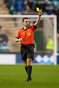 Referee Andrew Dallas shows a yellow card during the Ladbrokes Scottish Premiership match between Hibernian FC and Hamilton Academical FC at Easter Road Stadium, Edinburgh, Scotland on 22 January 2020.