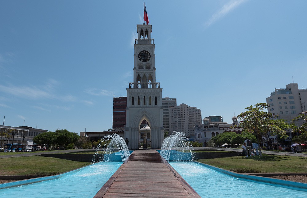 Iquique, Chile—April 9, 2018. A clock tower and fountains in the center of Iquique, Chile. Editorial use only.
