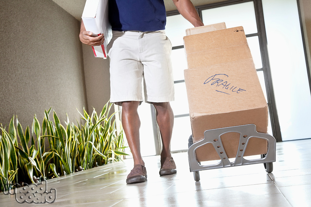 Low section of a man walking with packages on handtruck