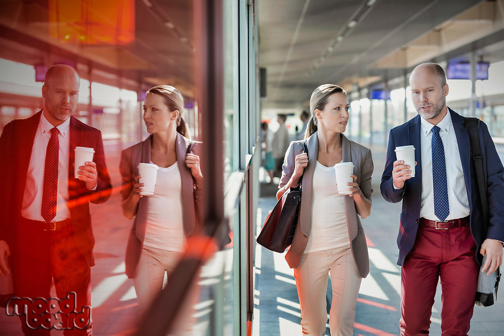 Portrait of businessman and businesswoman holding cup of coffee while walking and talking