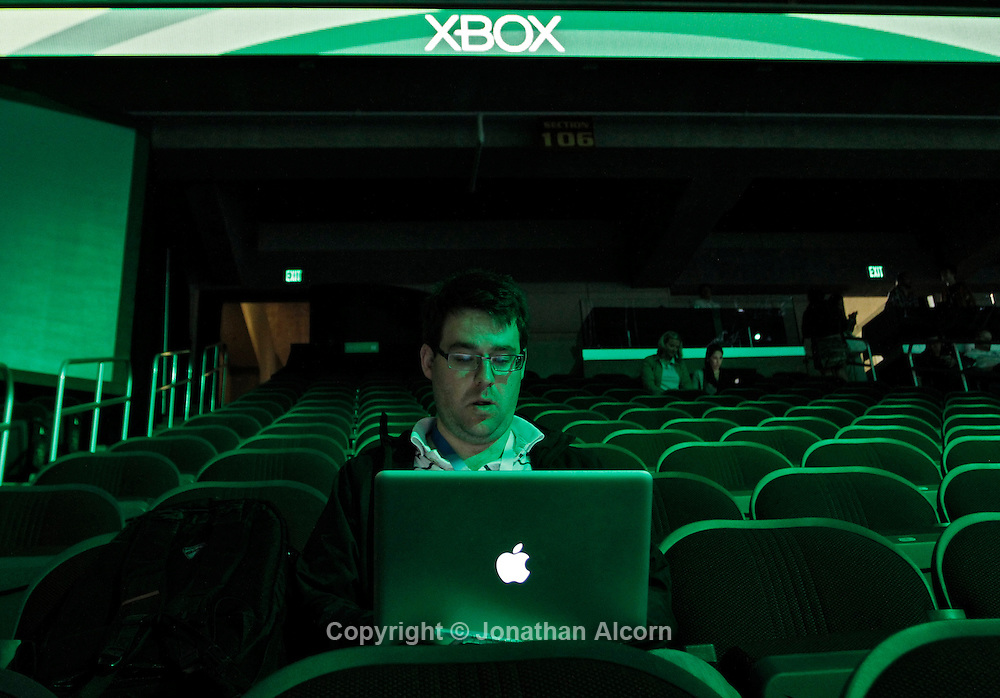 A man works on an Apple Macbook in the stands following Microsoft's XBOX E3 media briefing in Los Angeles, California, U.S., on Monday, June 4, 2012.  Photographer: Jonathan Alcorn/JTA