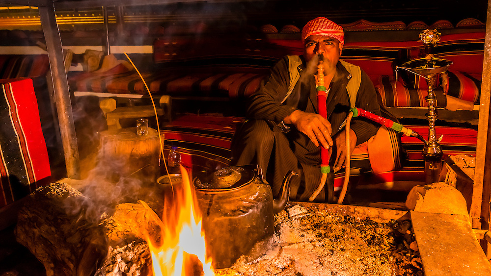 Bedouin man smoking sheesha (water pipe), Captain's Desert Camp, Arabian Desert, Wadi Rum, Jordan.