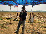 31 MARCH 2016 - NA SAK, LAMPANG, THAILAND: A farmer stands under a temporary shelter villagers put up in the Mae Chang Reservoir. Villagers come to the shelter to look at the ruins of their old village. The Mae Chang Reservoir in Lampang province was created more than 30 years ago when the Chang River was dammed. Five villages along the river were relocated to hillsides above the river. For the first time since it was flooded, the reservoir is nearly empty and the ruins of the old villages are visible. Many people who remember the old villages are coming down to the ruins to visit them. This part of Thailand hasn't received significant rain in months and many irrigation canals and streams are running dry.    PHOTO BY JACK KURTZ