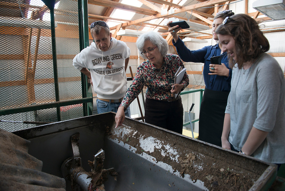 "Sustainability Coordinator at Bowling Green State University, Nick Hennessy, Director of Sustainability at Miami University, Yvette Kline, and Sustainability Coordinator at Oberlin College, Bridget Flynn examine the the machinery of the compost facility with the help of ""student sustainability expert Tess."" Photo by Olivia Wallace"