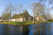 Nederland, Well, 20160314.<br /> Emerson College European Centre op het kasteel in Well, Limburg. De buitenste gracht om het kasteelcomplex met de Tiendschuur<br /> Kasteel Well is een fraaie waterburcht. Het huidige kasteel werd pas gebouwd in de vijftiende eeuw, maar kreeg pas later, in de zeventiende eeuw, zijn huidige aanzicht. Achter het huidige kasteel liggen de resten van een torenmolen uit de vijftiende eeuw. 