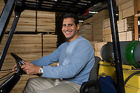 Mid-adult man driving forklift at warehouse