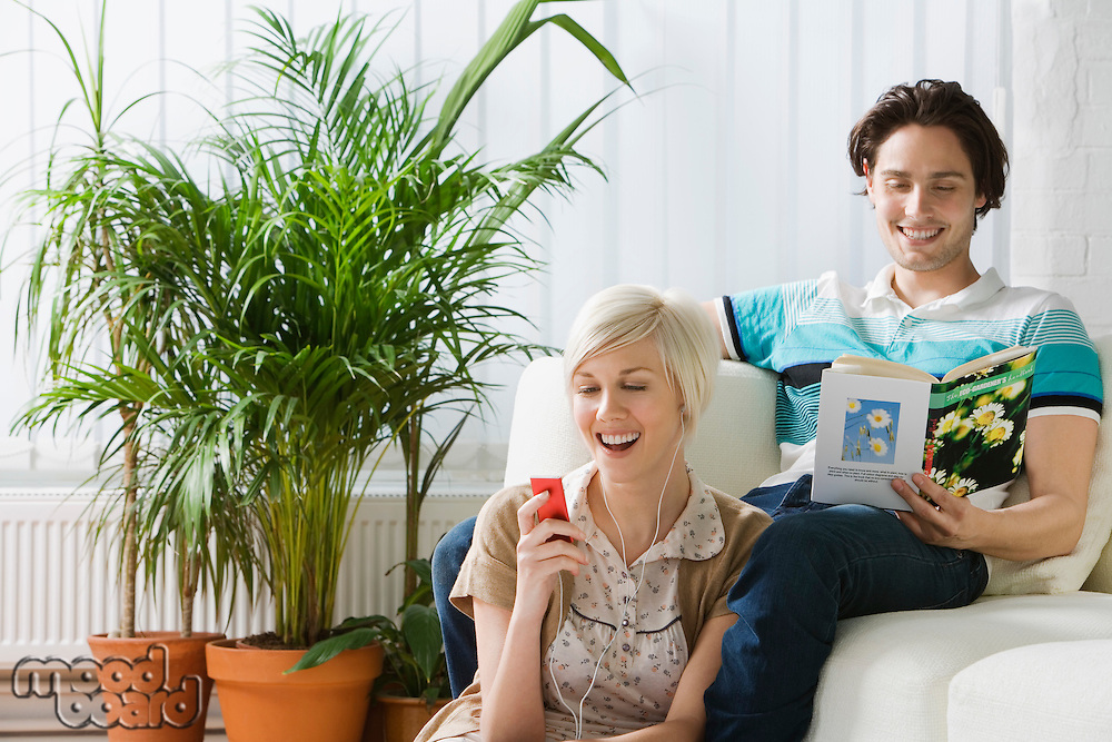 Young woman listening mp3 player next to man reading book on sofa