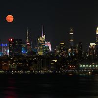 New York City full moon skyline photography showing the Empire State Building with its iconic midtown and westside cityscape. <br />