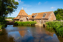 View of Preston Mill with waterwheel, millpond and doocot on River Tyne in East Lothian, Scotland , UK