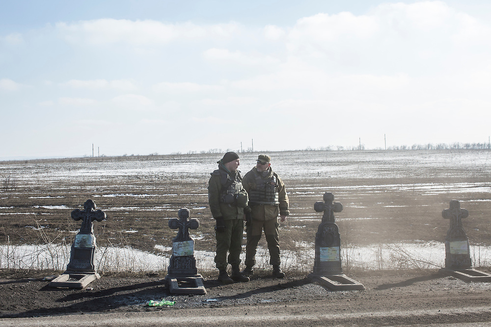 ZORYNSK, UKRAINE - FEBRUARY 20: Pro-Russian rebels stand by the road as military trucks leave the town of Debaltseve on February 20, 2015 in Zorynsk, Ukraine. Ukrainian forces withdrew from the strategic and hard-fought town after being effectively surrounded by pro-Russian rebels, though fighting has caused widespread destruction. (Photo by Brendan Hoffman/Getty Images) *** Local Caption ***