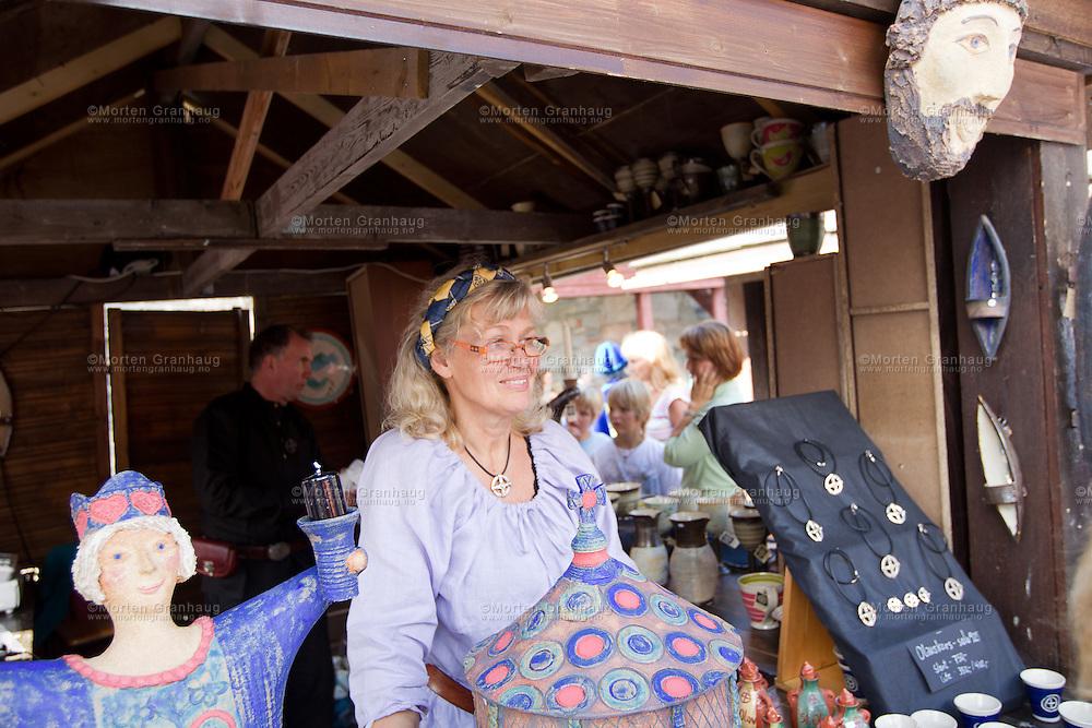 Fra historisk marked, Olavsfestdagene 2011...Marianne Fjærvik fra Amfora design. Marianne har vært med på Olavsfestdagene siden 2000 eller 2001, og sto da sammen med husflidshåndtverkerne. Etter hvert har hun jobbet nok til at hun har fylt sin egen bod, og uttrykk og design har blitt preget av deltakelsen hennes på Olavsfestdagene samt historien...Hun lager hvert år et Olavsskrin, som man vet sto i alle kirker. Årets skrin er dekorert med fredsliljer..Hun står sammen med Tom Nyhus, som jobber med sølv.