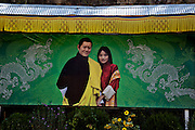 BU00010-00...BHUTAN - Portrait of the King and Queen welcoming visitors to the Land of the Thunder Dragon at Chhuzon, (the Confluence of the Paro Chhum and the Thimphu Chhu to make the Wang Chhu).
