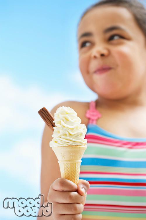 Girl (7-9 years) holding icecream focus on icecream