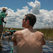 Man riding in a mokoro in the Okavango Delta. Model-released.