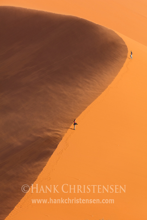 Visitors struggle to climb the face of Dune 49 as a wind storm blows clouds of sand into the air, Namib-Naukluft National Park, Namibia.