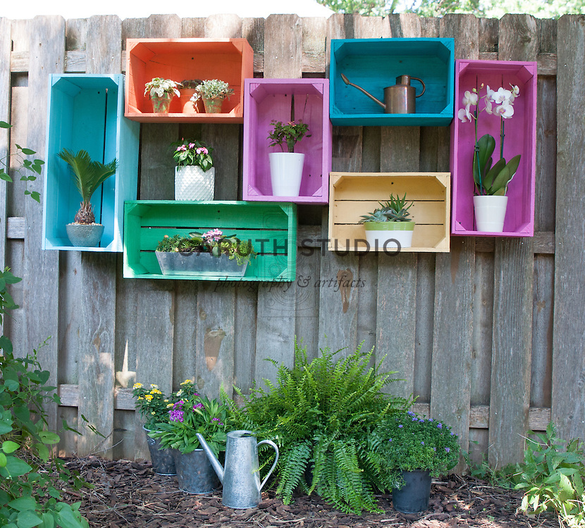 Painted wood crates on a fence