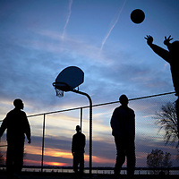 The sun sets behind a game of pick-up basketball at Bayview Park between friends and neighbors who live nearby on April 23, 2016, in Erie, Pa. Photo by Andy Colwell/Erie Times-News