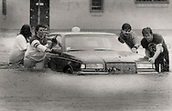 DIANE ROBERTS (LEFT), A PASSENGER IN THE CAR WHEN IT STALLED, WITH HELP OF FRIENDS PUSHES A FRIENDS CAR ON BIGELOW STREET.<br />