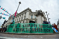 © Licensed to London News Pictures. 08/10/2019. LONDON, UK.  A banner erected by climate activists at a makeshift camp in Horse Guards Road outside HM Treasury, on day two of Extinction Rebellion's protest which is planned to close-down Westminster and other areas in the capital for two weeks.  Demonstrators are calling on the Government's immediate action to tackle the negative effects of climate change.  Photo credit: Stephen Chung/LNP