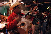 """MEXICO, Veracruz, Tantoyuca, Oct 27- Nov 4, 2009.  A trio of Huasteco musicians perform for """"cuadrillo"""" dancers. """"Xantolo,"""" the Nahuatl word for """"Santos,"""" or holy, marks a week-long period during which the whole Huasteca region of northern Veracruz state prepares for """"Dia de los Muertos,"""" the Day of the Dead. For children on the nights of October 31st and adults on November 1st, there is costumed dancing in the streets, and a carnival atmosphere, while Mexican families also honor the yearly return of the souls of their relatives at home and in the graveyards, with flower-bedecked altars and the foods their loved ones preferred in life. Photographs for HOY by Jay Dunn."""