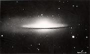 Astronomy: Spiral galaxy NGC 4594 (M 104) seen edge-on. Note the dark dust cloud along the central portion. Photograph c1910.