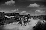 """Wary gazes from Saamaka Maroon artisanal gold miners as they leave their mining compound.  This large site for artisanal gold mining by independent Saamaka Maroon men near the fringes of the huge Rosabel Mine run by Iamgold, a Canadian gold mining corporation on Saamaka land.  ..In January 2011, Iamgold announced that it would increase its investment in the Rosebel Mine which would include investment in a second large dam.  The Afobaka Dam, built in the early 1960's, created Lake Brokopondo near Brownsweg, which already inundated many villages and covers 50% of Saramaka territory, That land was bequeath to the former escaped slaves in a treaty signed with their Dutch colonizers in 1762.  The second dam, to be built on Ndyuka Maroon land, would divert water into Lake Brokopondo via canal, raising the water level and would inundate several more Saamaka villages.  In the landmark 2007 decision for """"Saamaka v Suriname"""" at the Inter-American Court of Human Rights in Costa Rica, the court """"guaranteed territorial rights not just for Saamaka, but for all Maroons and indigenous people"""" in Suriname.  Still there has been no consultation with representatives of either the Saamaka or Ndyuka Maroon communities about the new dam-building project affecting the land of both groups of Maroons.   Near Brownsweg, Suriname."""