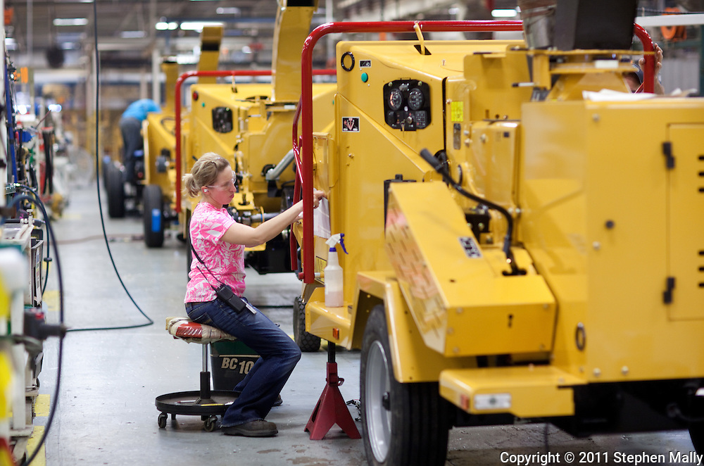 An employee applies stickers on a brush chipper on the assembly line in Plant 4 at Vermeer in Pella, Iowa on Thursday, July 28, 2011.