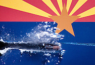 A .22 caliber bullet traveling at 1167 feet per second slices through a Arizona state flag card.  A 30,000 volt flash unit and chronometer custom built by Jasper Nance measures the speed of the bullet and calculates how long it will take to reach the target at a preset distance, the high speed flash then fires freezing the bullet. Cameras are setup on tripods, the shutters are opened for 13-seconds and the photographers quickly move to safety behind the firing line.  The weapon is fired and Nance's equipment does the rest. The photos were taken at night.
