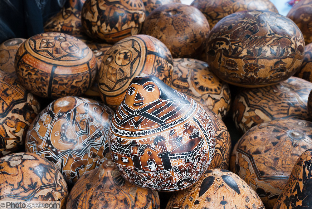 Painted gourds for sale, Otavalo, Ecuador, South America. The culturally vibrant town of Otavalo attracts many tourists to a valley of the Imbabura Province of Ecuador, surrounded by the peaks of Imbabura 4,610m, Cotacachi 4,995m, and Mojanda volcanoes. The indigenous Otavaleños are famous for weaving textiles, usually made of wool, which are sold at the famous Saturday market and smaller markets during the rest of the week. The Plaza del Ponchos and many shops tantalize buyers with a wide array of handicrafts. Nearby villages and towns are also famous for particular crafts: Cotacachi, the center of Ecuador's leather industry, is known for its polished calf skins; and San Antonio specializes in wood carving of statues, picture frames and furniture. Otavaliña women traditionally wear distinctive white embroidered blouses, with flared lace sleeves, and black or dark over skirts, with cream or white under skirts. Long hair is tied back with a 3cm band of woven multi colored material, often matching the band which is wound several times around their waists. They usually have many strings of gold beads around their necks, and matching tightly wound long strings of coral beads around each wrist. Men wear white trousers, and dark blue ponchos. Otavalo is also known for its Inca-influenced traditional music (sometimes known as Andean New Age) and musicians who travel around the world.