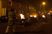 Late at night, bonfire societies parade the streets with burning barrels on wheels