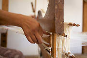 A close up of a womens hands working the loom.