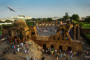20th August 2015, New Delhi, India. View of the semi-ruined mosque as worshippers gather for Namaz in the ruins of Feroz Shah Kotla in New Delhi, India on the 20th August  2015<br /> <br /> PHOTOGRAPH BY AND COPYRIGHT OF SIMON DE TREY-WHITE a photographer in delhi<br /> + 91 98103 99809. Email: simon@simondetreywhite.com<br /> <br /> <br /> The13th century fortress-city of Firoz Shah Kotla in Delhi is thronged weekly with thousands of supplicants seeking favour from supernatural beings of smokeless fire, - Djinns. These magical entities also known as Jinn, Jann or Genies spring from Islamic mythology as well as pre-Islamic Arabian mythology. They are mentioned frequently in the Quran and other Islamic texts and inhabit an unseen world called Djinnestan. Believers, mostly Muslim but from other faiths too, circumnavigate the ruins clutching dozens of photocopied requests, flower petals, incense, and candles. They visit the numerous niches and alcoves in the catacombs said to be occupied by different djinns and greet and salute the invisible occupants with offerings.  A copy of their requests, often with detailed contact information, photographs and even police reports to bolster the case is left with the 'Baba' before moving on to the next where the procedure is repeated - like making applications at different departments of a bureaucracy