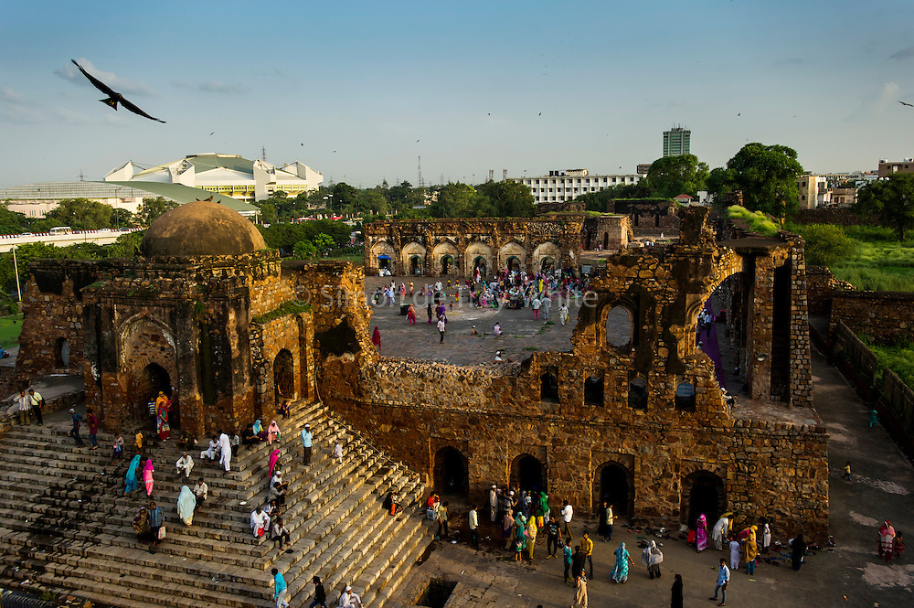 20th August 2015, New Delhi, India. View of the semi-ruined mosque as worshippers gather for Namaz in the ruins of Feroz Shah Kotla in New Delhi, India on the 20th August  2015<br /> <br /> PHOTOGRAPH BY AND COPYRIGHT OF SIMON DE TREY-WHITE a photographer in delhi<br /> + 91 98103 99809. Email: simon@simondetreywhite.com<br /> <br /> <br /> The13th century fortress-city of Firoz Shah Kotla in Delhi is thronged weekly with thousands of supplicants seeking favour from supernatural beings of smokeless fire, - Djinns. These magical entities also known as Jinn, Jann or Genies spring from Islamic mythology as well as pre-Islamic Arabian mythology. They are mentioned frequently in the Quran and other Islamic texts and inhabit an unseen world called Djinnestan. Believers, mostly Muslim but from other faiths too, circumnavigate the ruins clutching dozens of photocopied requests, flower petals, incense, and candles. They visit the numerous niches and alcoves in the catacombs said to be occupied by different djinns and greet and salute the invisible occupants with offerings.  A copy of their requests, often with detailed contact information, photographs and even police reports to bolster the case is left with the &lsquo;Baba&rsquo; before moving on to the next where the procedure is repeated - like making applications at different departments of a bureaucracy
