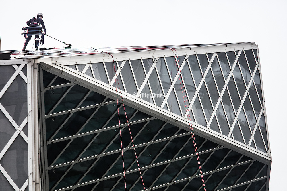 Tuesday, November 29, 2016.   Window washers (there are two, one is hidden) start the task of cleaning 9,994 exterior windows on the downtown Seattle Library designed by Rem Koolhaas, enough windows to cover 5 1/2 football fields.   <br />