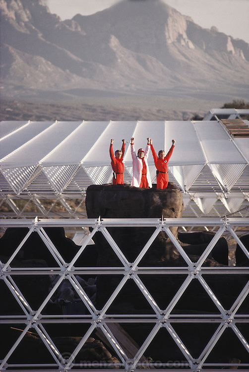 Biosphere 2 Project undertaken by Space Biosphere Ventures, a private ecological research firm funded by Edward P. Bass of Texas.  Three of the eight candidates for the Biosphere 2 Project, seen at the top of the Biosphere 'mountain' during construction (before the glass canopy covered it).  Biosphere 2 was a privately funded experiment, designed to investigate the way in which humans interact with a small self-sufficient ecological environment, and to look at possibilities for future planetary colonization. 1990