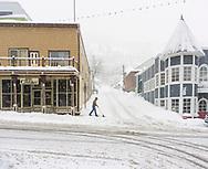 Man wearing cowboy hat shoveling snow on Historic Main Street, Park City, Utah. USA.