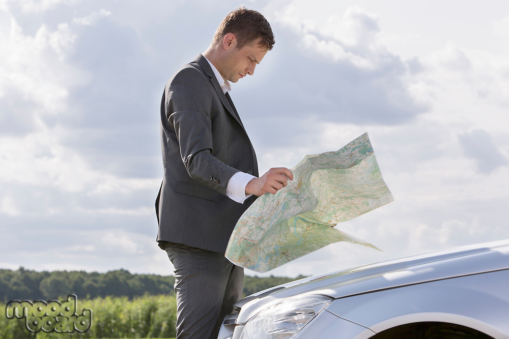 Side view of young businessman reading map by car at countryside