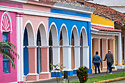 People walk past the colorful colonnade style buildings in Tlacotalpan, Veracruz, Mexico. The tiny town is painted a riot of colors and features well preserved colonial Caribbean architectural style dating from the mid-16th-century.