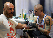 Garden City, New York, USA. September 13, 2015. LUKE PALAN, a tattoo artist from Vegas, is tattooing a man's arm at the United Ink Flight 915 Tattoo convention at the Cradle of Aviation Museum in Long Island. The bearded man is wearing a Psycho Bunny white and red T-shirt.