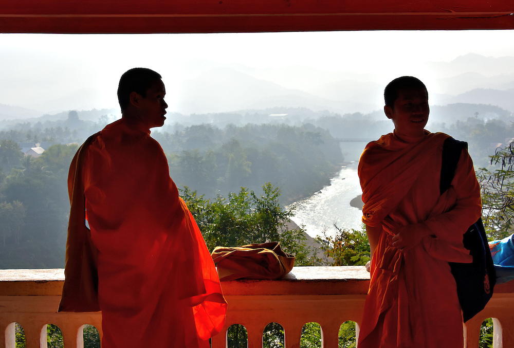 Novice Monks on Terrace at Mount Phousi in Luang Prabang, Laos  <br /> These novice monks, called samaneras, were on a pilgrimage to Mount Phousi in Luang Prabang, Laos.  They stopped half way up the 328 foot holy mountain to visit a nearby cave with the imprint of Buddha's foot.  Then they stood on this terrace at Wat Tham Phu Si overlooking the Nam Khan River before proceeding to the summit.