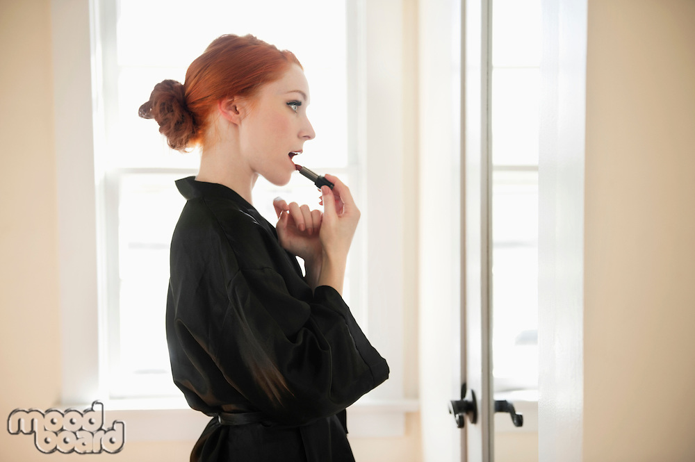 Profile view of a young woman in robe applying lipstick