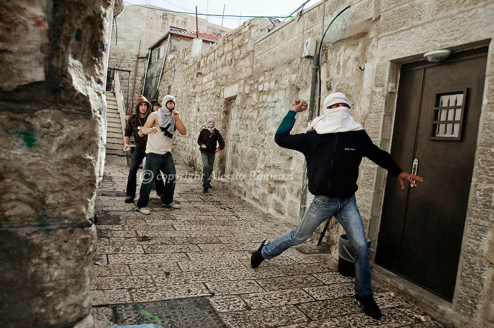 JERUSALEM : Palestinians youths hurl stones at Israeli policemen, not seen, during clashes in Jerusalem's Old City, Sunday, Feb. 28, 2010. Israeli police forces stormed the most contentious holy site in Jerusalem on Sunday to disperse masked Palestinian protesters hurling objects at visiting foreign tourists..© ALESSIO ROMENZI