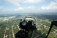 A view from the nose of an airborne B-17 Flying Fortress over central Florida.  The device at center is a Norden Bombsight and was top-secret during WWII.