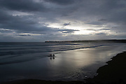 Lahinch beach, Co. Clare, Ireland at dusk, with Liscannor in the background and two surfers coming ashore.