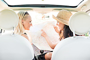 Rear view of happy female friends reading map in car
