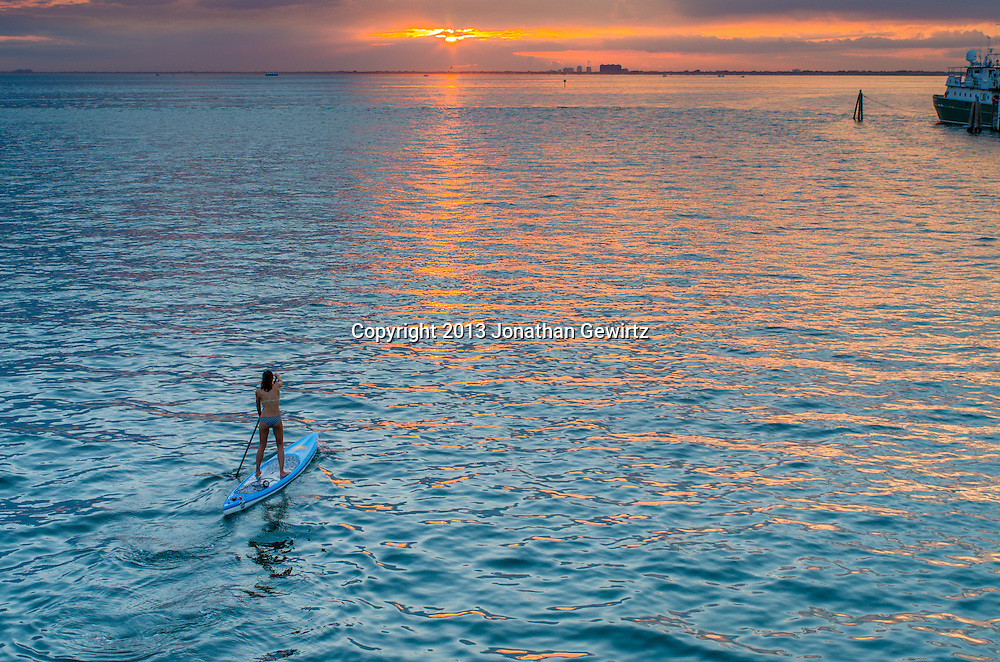 A young woman paddles toward the setting sun in Bear Cut between Virginia Key and Key Biscayne, Florida. <br />