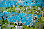 The Deep Eddy Mosaic Mural nearing completion, Austin, Texas, June 29, 2011. Under the auspices of Friends of Deep Eddy, art therapist Wanda Montemayor and ceramic artist Lisa Orr involved students from nine different middle and high schools to create the largest mosaic mural in Austin. This mural transformed the concrete ramp that connects the pools parking lot to the Lake Lady Bird Hike and Bike Trail into an historical portrait of the pools long and rich history that stretches back to 1915...