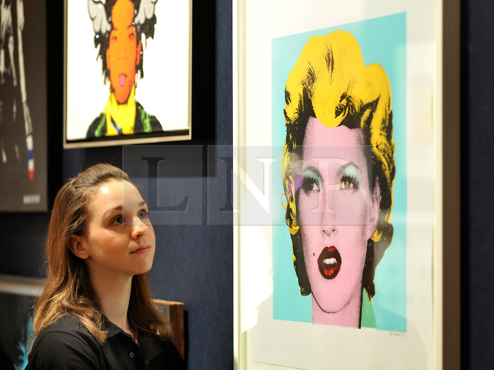 © Licensed to London News Pictures. 23/03/2012. London, UK. Bonham's staff member Victoria Livesey looks at one of the highlights of the sale, a screen print of British supermodel Kate Moss, 2005, inspired by Andy Warhols iconic Marilyn Monroe series, which has been estimated at £30,000  50,000. A photocall of Bonham's Urban Art Sale including Seventeen art works by the celebrated graffiti artist, Banksy, which are to be sold at Bonhams, London, ahead of the Urban Art Sale, which takes place on 29 March 2012. . Photo credit : Stephen SImpson/LNP