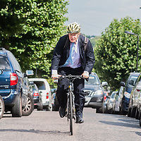 London, UK - 7 August 2014: The Mayor Boris Johnson arrives with his bike to meet Rabbi Oscher Schapiro and the Orthodox Jewish community in Stamford Hill, London