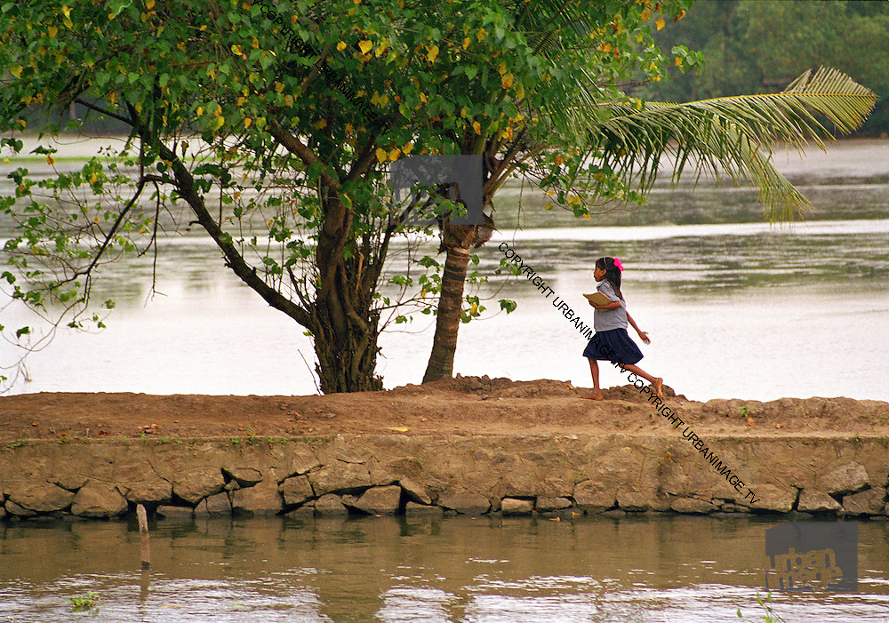 Girl walks home from school along the flooded backwaters - Kerala India